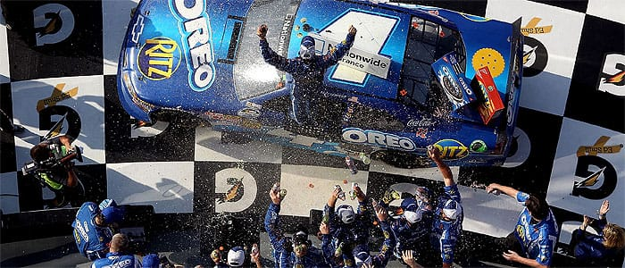 Tony Stewart climbs out of the No. 4 Oreo/Ritz Chevrolet in victory lane after winning the Drive4COPD 300 by .007 seconds