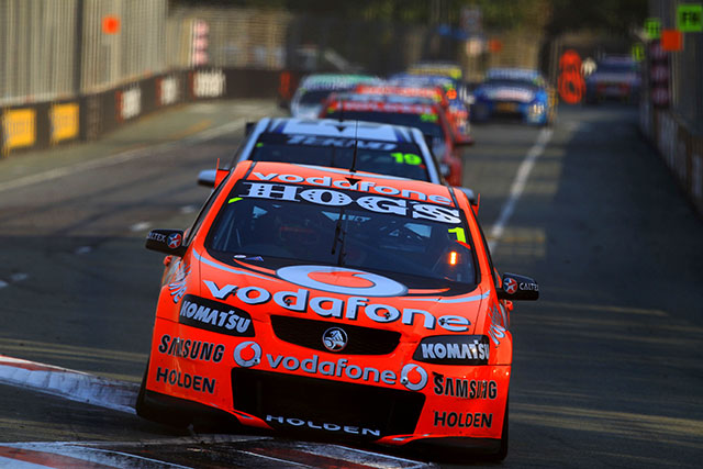 TeamVodafone's Jamie Whincup and Sébastien Bourdais held on to win the opening race of the Armor All Gold Coast 600 surviving an incident-filled race to extend Whincup's grip on the 2012 championship