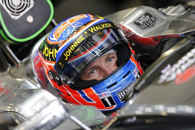 Jenson Button waiting in his car in the garage.