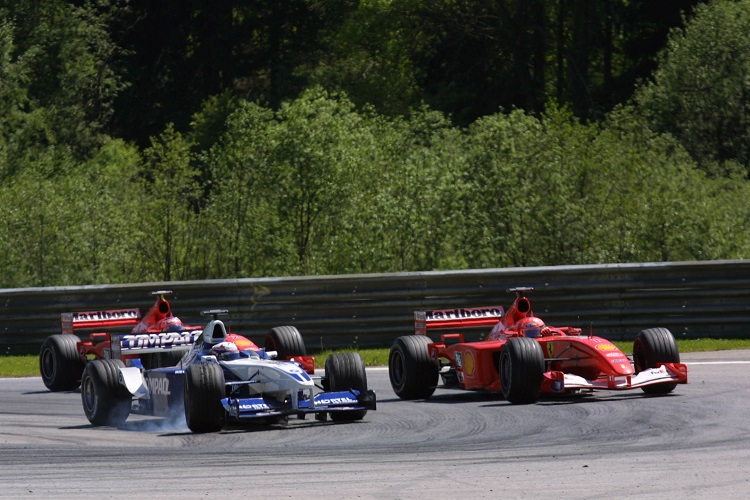 Juan Pablo Montoya attempts to hold off Michael Schumacher (Credit: LAT Photographic)