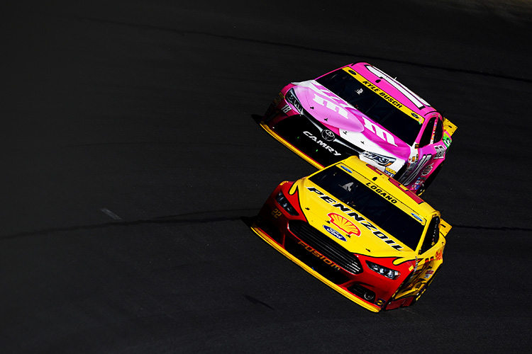 CHARLOTTE, NC - OCTOBER 11:  Joey Logano, driver of the #22 Shell Pennzoil Ford, races Kyle Busch, driver of the #18 M&M's Pretty In Pink Foundation Toyota, during the NASCAR Sprint Cup Series Bank of America 500 at Charlotte Motor Speedway on October 11, 2015 in Charlotte, North Carolina.  (Photo by Josh Hedges/Getty Images)