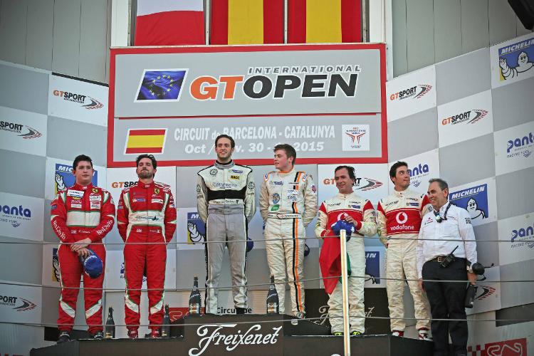 Watson stands atop the Catalunya podium ....... - Credit: McLaren Media