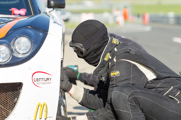 A crew member changes a tyre on a Centry Motorsport Ginetta during a Britcar Endurance race.