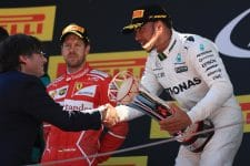 Lewis Hamilton accepts a first-place trophy whilst a disappointed Sebastian Vettel looks on