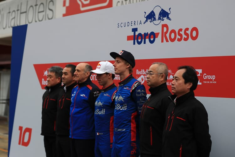 Toyoharu Tanabe, and other Toro Rosso and Honda representatives, stand in front of Toro Rosso advertising