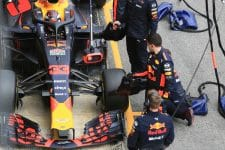 Red Bull pit stop crew watch as Max Verstappen pulls into his pit box