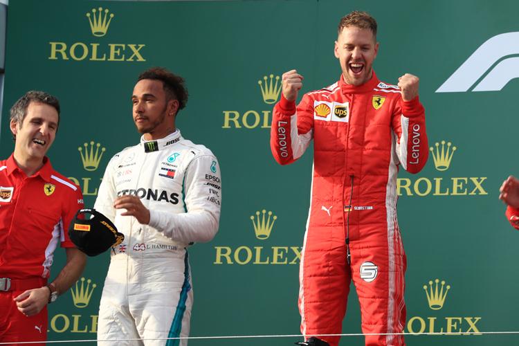 Lewis Hamilton looks dismayed on the podium next to a triumphant Sebastian Vettel