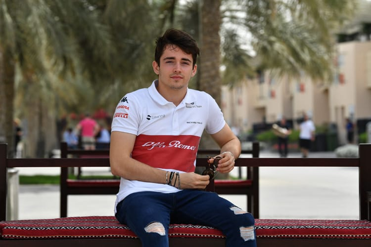 Charles Leclerc sits on a bench