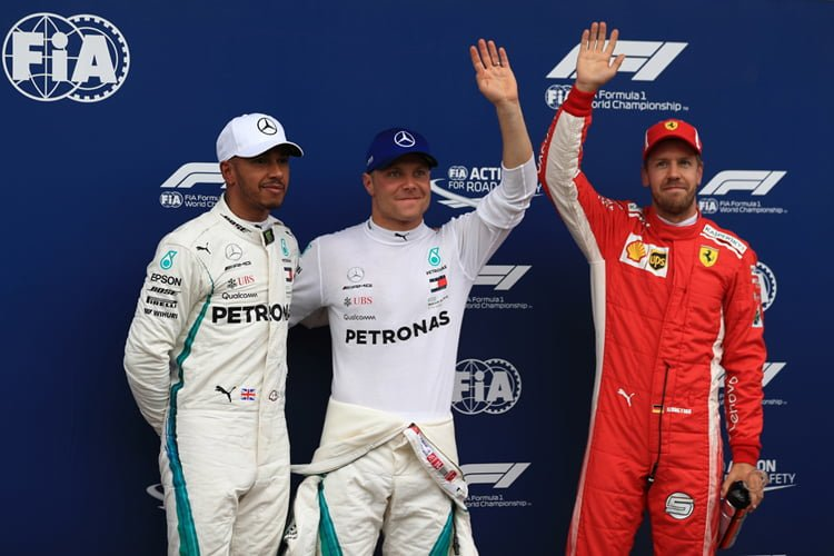 Lewis Hamilton stands next to Valtteri Bottas and Sebastian Vettel after qualifying for the Austrian Grand Prix
