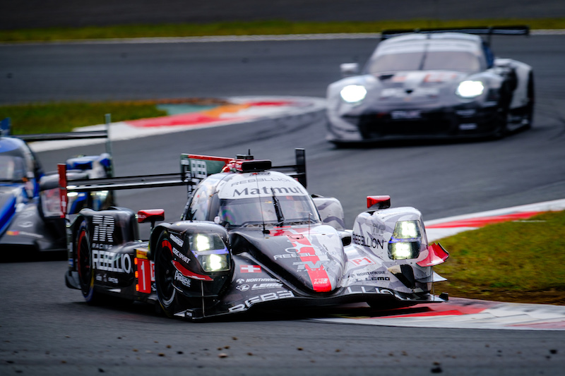Rebellion Racing #1 on track at Fuji Speedway, leading an LMP2 and the #88 Dempsey-Proton Racing, 2019
