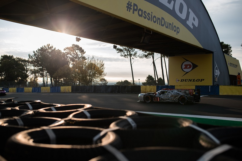 The #1 Rebellion Racing LMP1 car driving through Dunlop at the 2020 24 Hours of Le Mans at sunrise